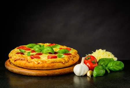 Tasty Fresh Pizza with Cooking Ingredients on dark background Stock Photo - 77940849