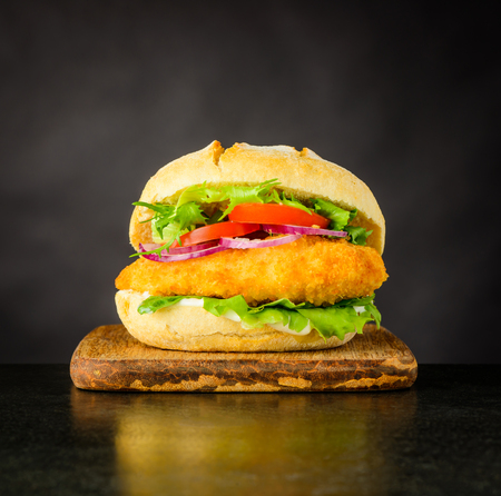 Chickenburger Fast Food Sandwich with Meat and Vegetables on Dark Background Stock Photo - 79411064
