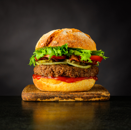 Sandwich Burger fast food with Meat and Vegetables on Dark Background Stock Photo