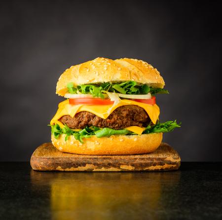 Cheeseburger Fast Food Sandwich on Dark Background Stock Photo