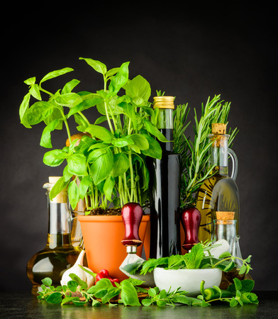 Still Life with Fresh Green Basil Herbs, Olive oil, Mezzaluna Herb-chopper and Pestle and Mortar Kitchen Utensil