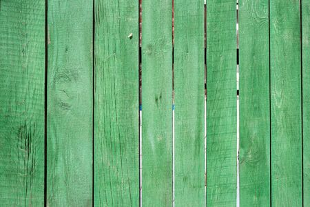 Background image of a wooden fence. Texture of painted wood. Wooden boards. Old fence painted with green paint. Text space. Wallpaper. Texture for exterior and interior. Wood material for construction