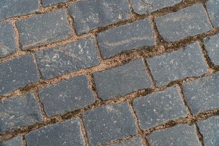 Background image of a surface of a cobblestone road. Wallpaper. Substrate for text. Detailed texture of paving stones. Idea for exterior and interior. Geometric pattern. Top view. 版權商用圖片