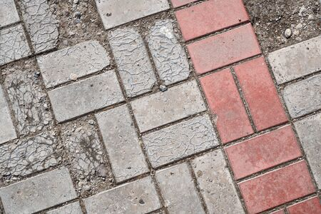 Background image of pavement cover. Detailed texture of paving slabs. Text space. Wallpaper. Footpath cover. Texture for the exterior. Cracks on the paving slabs. Top view. Red and gray paving tiles. 版權商用圖片