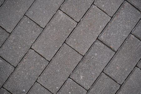 Background image of the surface of the sidewalk. Wallpaper. Substrate for text. Detailed texture of a pedestrian walkway with paving tiles. Paving slabs in the exterior. Top view.