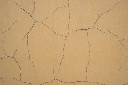Background image of an old wall. The paint cracked from time to time. Old concrete wall in the cracks. The texture of the painted wall. Text space. Texture for interior and exterior. Sprawling cracks.
