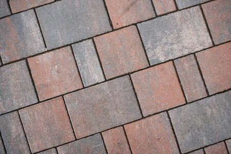 Background image of neatly laid paving slabs. Wallpaper. Substrate for text. Detailed texture of a tiled path. Paving slabs in the exterior. The surface of the road for pedestrians.