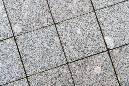 Background image of pavement surface. Wallpaper. Substrate for text. Detailed texture of a pedestrian walkway with paving tiles. Paving slabs in the exterior.