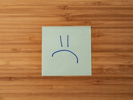 Sticker depicting the symbol of a sad emoticon. Paper sticker pasted on a wooden surface. Self-adhesive paper sheet. A piece of paper on a wooden board. Reminder for action. Paper sheet for notes.