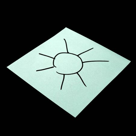Paper sticker with the image of the symbol of the sun. Isolated object on a black background. Paper texture. Sticky note. A piece of paper for notes. Self-adhesive piece of paper. Imagens
