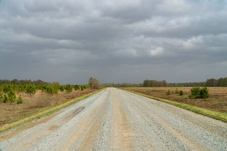 Background image of a road going into the distance. Asphalt road. Highway. Road markings. A road running through the forest. Let over the horizon. Siberian spring roads. Green Forest.