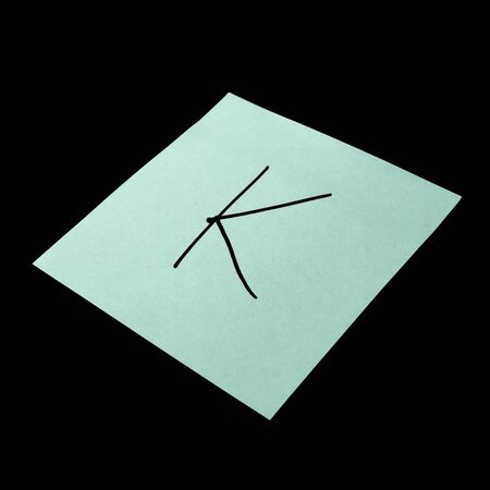 Paper sticker with the image of the letter k. Isolated object on a black background. Paper texture. Sticky note. A piece of paper for notes. Self-adhesive piece of paper. Imagens