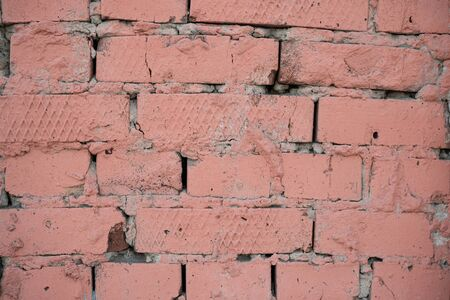 Background image of a painted brick wall. Sloppy brickwork. Detail brickwork texture. Texture for the interior. A wallpaper for the desktop. Text space. Painted in pink. Brick in construction. Imagens