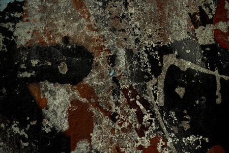 The texture of the old concrete wall covered with paint. Texture of cracked old paint. A background image of a helmet painted wall. Old graffiti on a concrete wall shot at close range. Graphic resources abstract textured background.