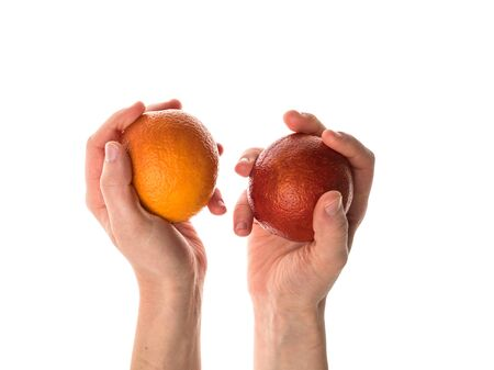 The blood orange is a variety of orange with crimson, almost blood-colored flesh. Female hand holds a bloody orange. Isolated on a white background. Hand of a white woman. Detailed photo.