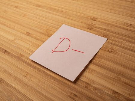 Sticker depicting the letter d. Paper sticker pasted on a wooden surface. Self-adhesive paper sheet. A piece of paper on a wooden board. Reminder for action. Paper sheet for notes.