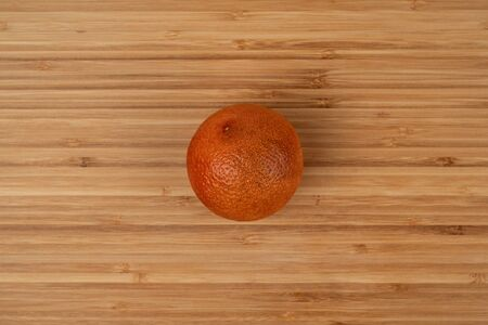 The blood orange is a variety of orange with crimson, almost blood-colored flesh. Image of a ripe orange on a wooden surface. Wood texture. Detailed photo. Soft shadows. Top view close-up. Imagens