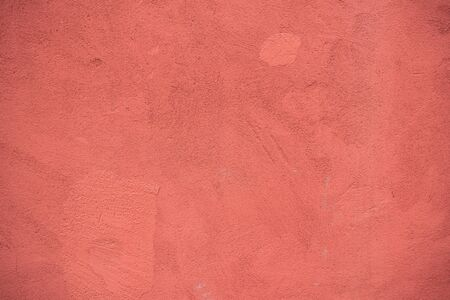Background image of painted concrete wall. Wallpaper. Text space. Texture for interior and exterior. Red paint. Detailed texture of uneven concrete surface. Texture of dried paint. Graphic resources.