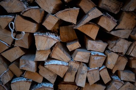 Background image of woodpile. Firewood is neatly stacked. Birch logs. Firewood for kindling a stove. Warehouse with firewood. A closeup. Background for text. Stock of firewood for the winter. Imagens