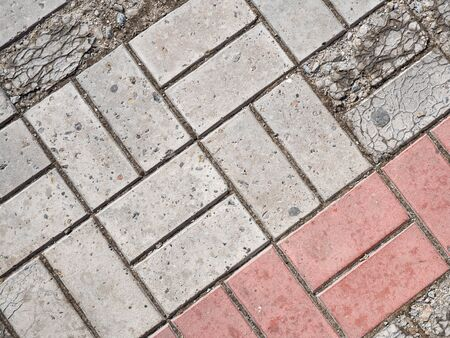 Background image of pavement cover. Detailed texture of paving slabs. Text space. Wallpaper. Footpath cover. Texture for the exterior. Cracks on the paving slabs. Top view. Red and gray paving tiles. Imagens