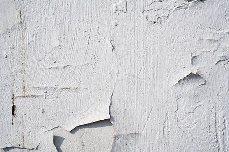 Background image of a white wall. The white paint is cracked. Old concrete wall in the cracks. Texture of the painted wall. Wallpaper. Text space. Detailed texture. Texture for interior and exterior. Imagens