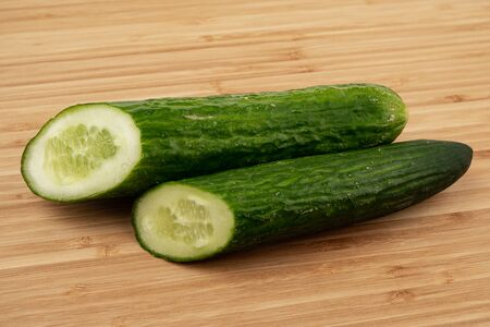 Cucumber on a wooden background. Wooden plank. Harvest fresh cucumbers. Ripe vegetable. Wood texture. Green smooth skin. A slice of cucumber. Vegetable diet. Proper nutrition. Ingredient for the salad Imagens