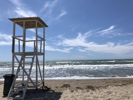 A white lifeguard tower on the beach .