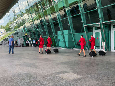 Flight attendants ,walking with her luggage, back view