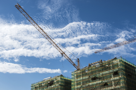 Tower crane at the construction site of blue sky and white clouds.