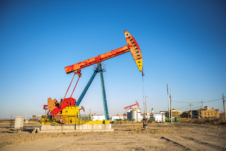 Oil pumps are running in the sunset at the oil field.