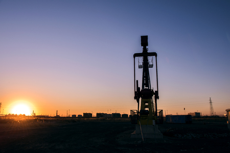 Oil pumps are running in the sunset at the oil field. The outline of the pumping unit. Stock Photo