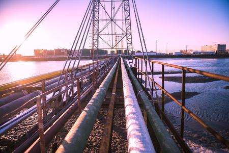 Oilfield pipeline bridge in sunset background