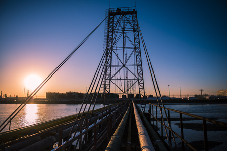 Oilfield pipeline bridge in sunset background