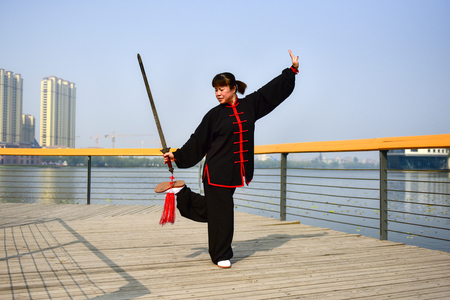 Luannan County, Hebei Province, China - May 11, 2019: an Asian woman practices Chinese Taijiquan in a park as a fitness exercise.