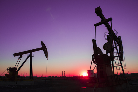 Oil pumps are running in the sunset at the oil field