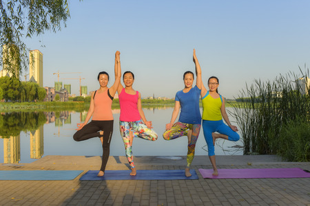 Luanan county, hebei province, China - September 1, 2019: do yoga exercises during the summer to keep fit and relax yoga lovers at the green park, a healthy lifestyle concept