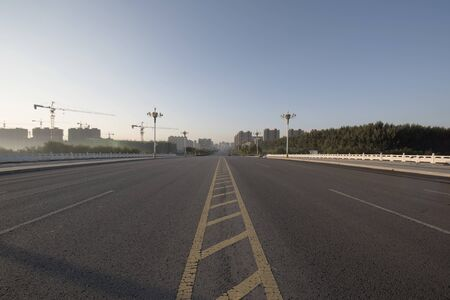 Asphalt road and beautiful blue sky in the background of sunrise