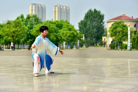 Tangshan, hebei province, China -- May 11, 2019: a Chinese woman performs tai chi at a square Редакционное