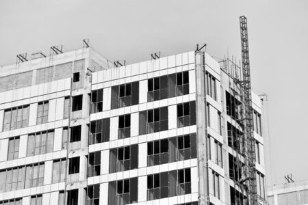 Close-up of steel frame under construction under blue sky background, black and white effect