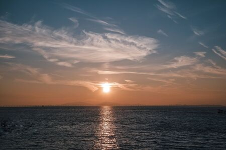A hazy view of the sunrise over the sea