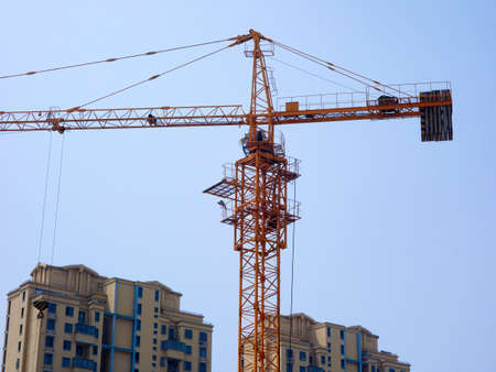 The tower crane on the construction site is busy working Фото со стока