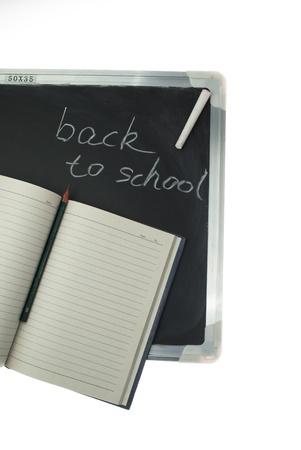 Notebook and little blackboard,the words Back to School written in chalk on the blackboard. photo