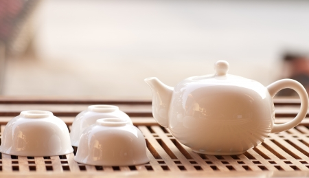 tea cups with teapot in teaboard photo
