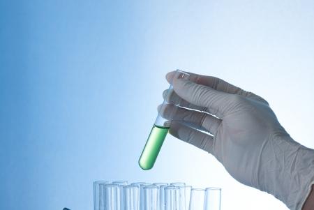 bureta: Un tubo de ensayo en la mano con agua de color