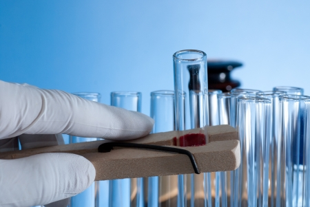 Hand holding a test-tube by test tube holder Stock Photo - 17833518