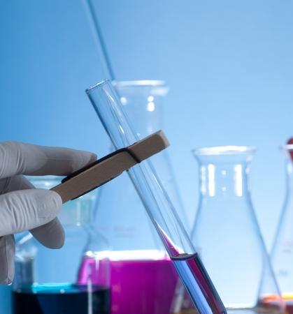 test tube holder: Hand holding a test-tube by test tube holder