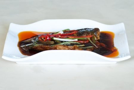 The roasted fillet of tilapia served with capsicum photo