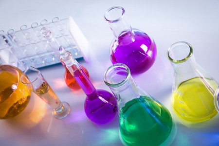 liquids: Laboratory glassware with various colored liquids on table Editorial