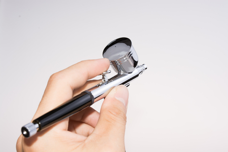 airbrush: Airbrush on a white background with a hand.