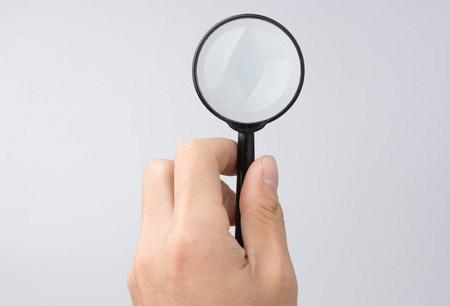 Hand?holding?magnifying?glass?on?a?white?background